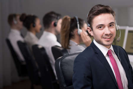 professionalist: Young male consultant is gently smilling while his co-workers are making conversations with clients