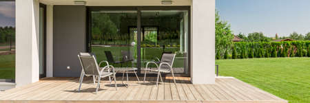 Panoramic close-up of a terrace in a modern suburban house, with board deck and garden furniture