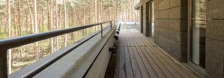 baranda para balcon: Muy amplio balcón de una vivienda unifamiliar en el medio de un bosque de pinos