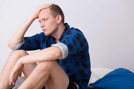 homme triste: Prise de vue d'un jeune homme triste assis sur son lit