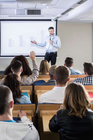 lecture theatre: Academic teacher explaining something to his students, using a bar graph displayed on a screen Stock Photo