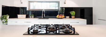 白い家具、四角形のウィンドウ最初地面にガスコンロと現代的なシンプルなキッチン 写真素材