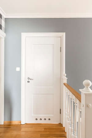 balustrade: Grey corridor with white doors and simple wooden balustrade