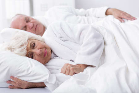 infatuation: Older married couple lie in bed. The husband is asleep and the wife has worried expression on her face