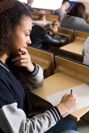 lecture theatre: Close-up of a female student writing exam answers on an answer sheet Stock Photo