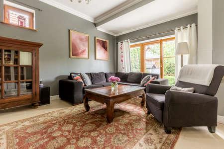 muebles antiguos: Amplia sala de estar con la ventana grande, muebles antiguos y alfombras de lana decorativo Foto de archivo