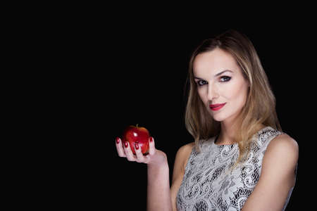 subtly: Portrait of an appealing woman on the black background, holding an apple and subtly smiling at the camera