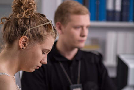 testify: Image of a young woman giving evidence, police officer in the background Stock Photo