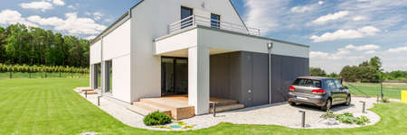Panoramic photo of a modern house in the country with a car on the driveway in front of it