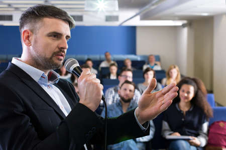 smartly: Professionally looking university teacher, holding a microphone while explaining something to a group of students