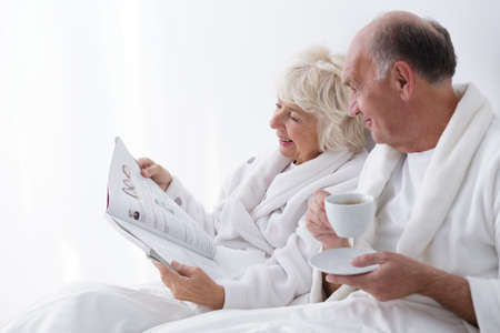 senility: Elderly couple relaxes in the morning with coffee and newspaper