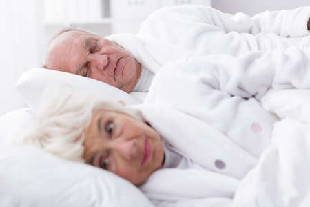 senility: Older woman is already awaked and her husband is still sleeping Stock Photo