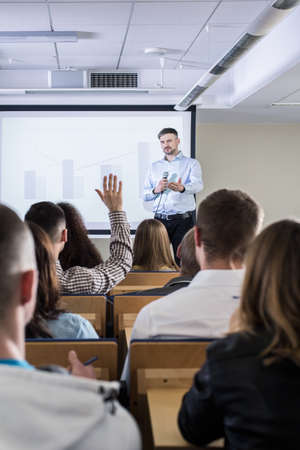 lecture theatre: Lecture room filled with students, with an academic teacher asking questions next to bar graphs displayed behind him