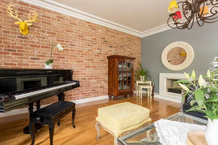 antique furniture: Stylish living room with piano, antique furniture and decorative brick wall Stock Photo