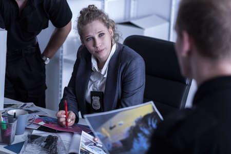 女性警察官、机の横に座っているバッジと 2 人の警官と話しています。 写真素材