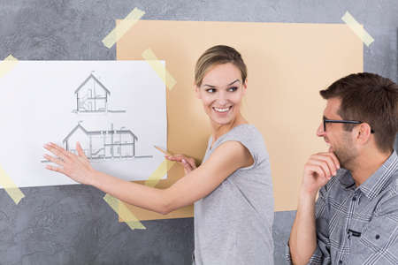 company person: Happy man and woman analyzing architectural house project