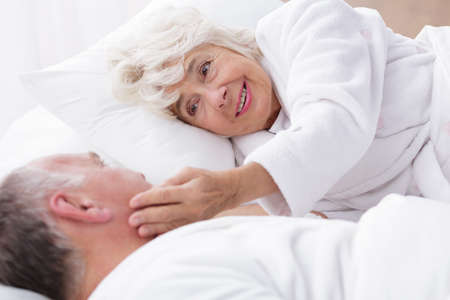 senility: Elderly couple lying in bed in the morning. Woman is gently touching her husband face