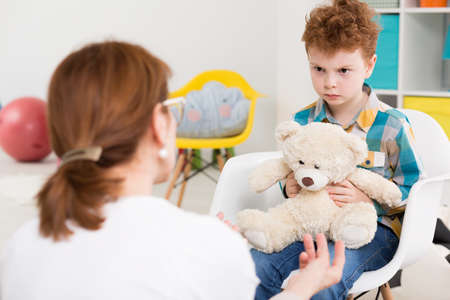 angry teddy: Shot of a little angry boy holding his teddy bear during a therapy session with his psychologist