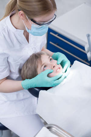 office tool: Young boy sitting on a dentists chair gritting teeth with the stomatologist with protective gloves and mask behind
