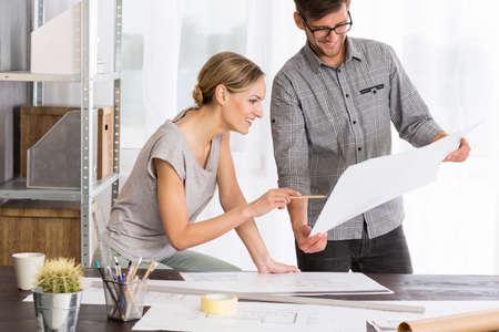 el hombre y la mujer feliz que analizan junto nuevo proyecto, de pie al lado del escritorio cubierto de papeles