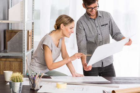 Happy man and woman analyzing together new project, standing beside desk covered in papers