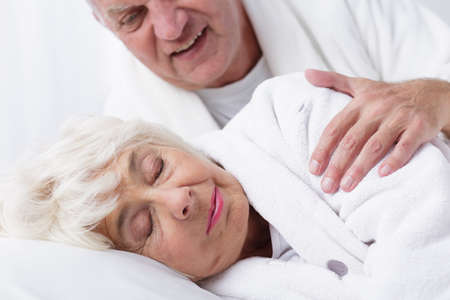 senility: Older man touches the shoulder of his sleeping wife