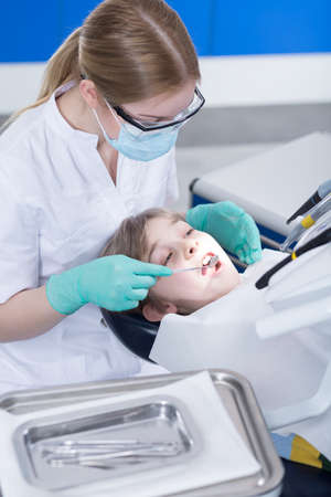 stomatologist: Young boy on a dentists chair with a stomatologist in protective gloves, mask and googles behind him and looking at his teeth