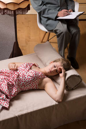 psychoanalysis: Depressed woman is lying on a cozy psychiatrist couch Stock Photo