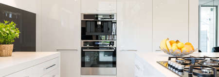 fitted: Very bright and high-polished kitchen with white furniture unit and built in oven and coffee maker