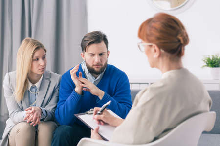marital: During marital therapy husband explains the problems to the therapist Stock Photo