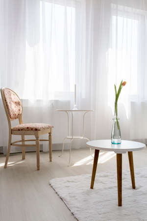 table and chairs: Shot of a living room with a big window Stock Photo
