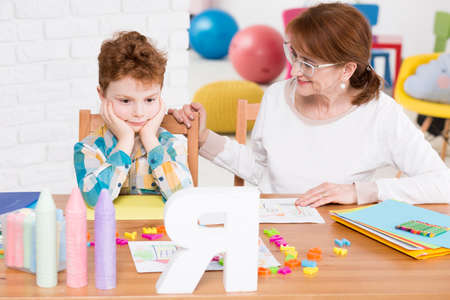 articulation: Confused little boy having a speech therapy session in a colourful office, sitting with his psychologist at a table full of educational materials