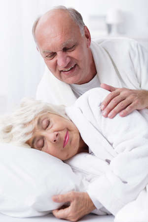senility: Older man by touching  the shoulder of his sleeping wife is trying to wake her up