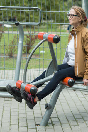 open air: Woman is sitting on exercise equipment focusing perform another repetition Stock Photo