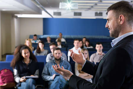 Foto del perfil de un profesor académica exitosa dando una charla animada con un grupo de estudiantes