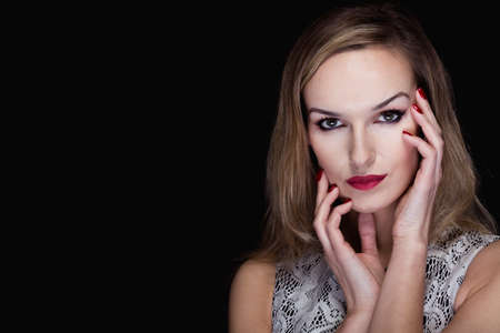 contrast: Contrasting portrait of a beautiful woman in seductive make up, touching her face with her hands Stock Photo