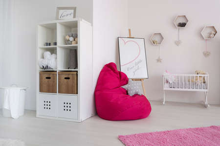 Fragment of a very bright newborns room with a fuchsia sit sack next to a white cradle