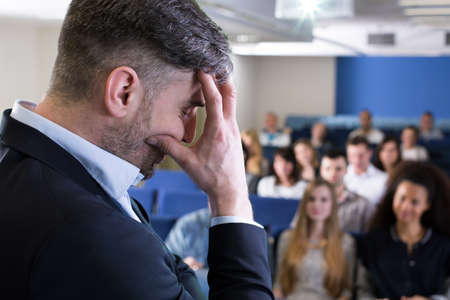 lecture theatre: Close-up of a young academic teacher in a lecture room filled with students, hiding his face in his hand in a frustrated pose