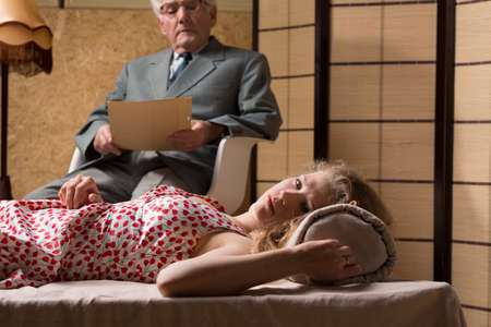 psychoanalysis: Senior psychotherapist looks at the notes about patient during the session