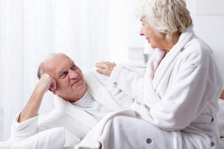 senility: Older woman touches the arm of her husband who is lying in bed