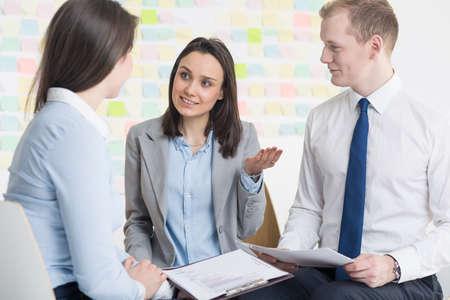 verlobung: Drei Mitarbeiter sitzen auf Stühlen im Kreis und freundlich diskutieren