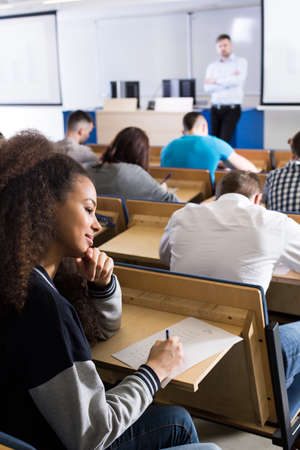 lecture theatre: Dark-skinned female student writing on a piece of paper in a lecture room next to her friends also taking the exam Stock Photo