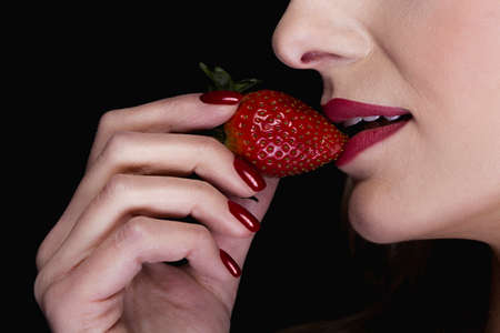 beautiful black woman: Close-up of a sexy woman holding a strawberry close to her red lips