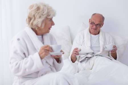 senility: Elderly couple after waking up is drinking coffee and relax with a newspaper