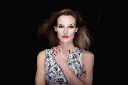 femme fatale: Portrait of a good-looking woman on the black background, with wind blowing her hair Stock Photo