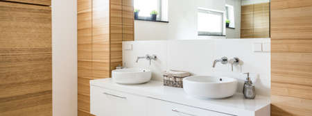 washbasins: Fragment of a very bright bathroom with wood-imitating tiles and two round ceramic washbasins