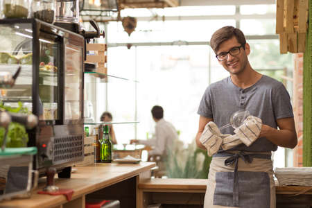 man at work: Shot of a young owner standing inside his coffee shop Stock Photo