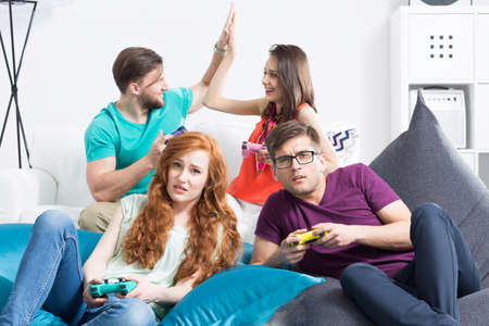 gamepads: Dissapointed young couple with gamepads sitting on large bean bags with the other couple celebrating victory in the background