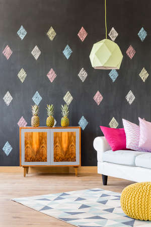Stylish flat with blackboard, pattern carpet, exotic commode, sofa, pouffe and ceiling lamp Stock Photo