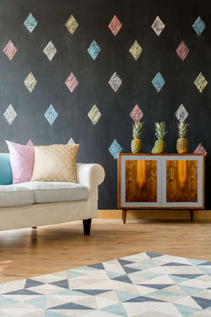 commode: Small living room with blackboard, white sofa, pastel cushions, pattern carpet and exotic commode Stock Photo